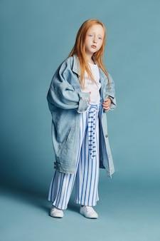 Piękna rudowłosa dziewczynka z długimi włosami w dużej niebieskiej długiej dżinsowej kurtce