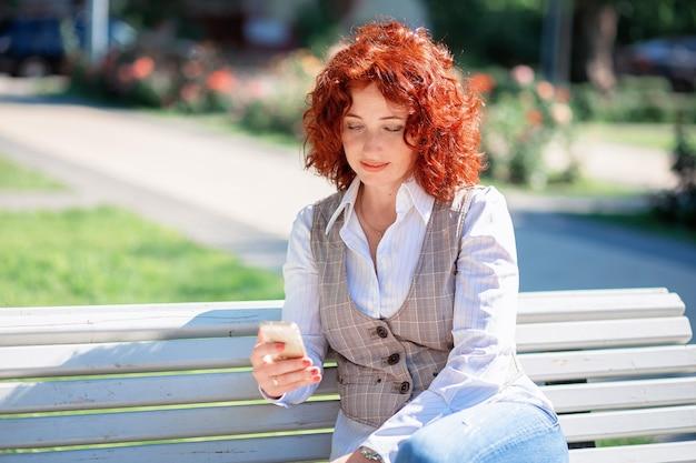 Piękna rudowłosa kobieta latem siedzi na ławce w parku i korzysta z telefonu