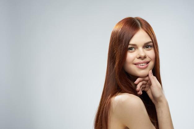 Piękna rudowłosa kobieta nagie ramiona kosmetyki długie włosy glamour jasnym tle. wysokiej jakości zdjęcie