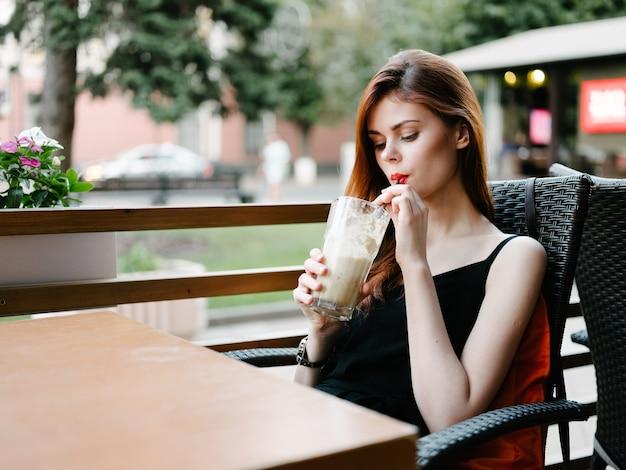 Piękna rudowłosa kobieta przy stole w kawiarni modelu z bliska portret ulicy