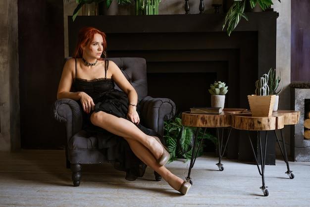 Piękna rudowłosa kobieta w czarnej sukience i seksownych butach siedzi na krześle na tle ...