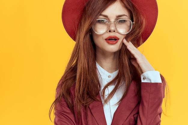 Piękna rudowłosa kobieta w garniturze i czerwonym kapeluszu, stylowy wizerunek biurowy