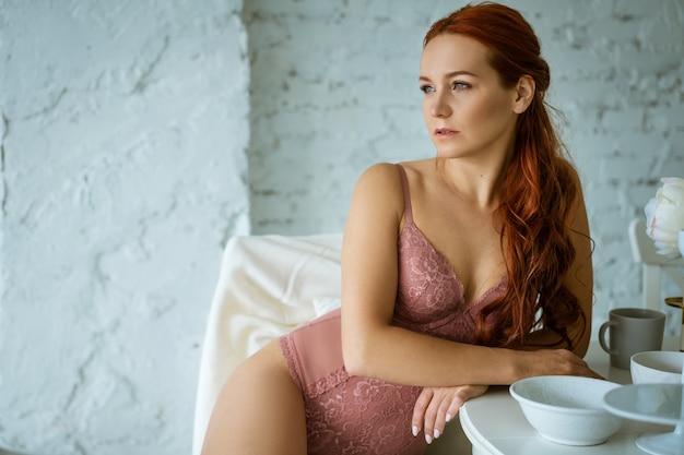Piękna rudowłosa kobieta w różowej bieliźnie kabaretki w kuchni