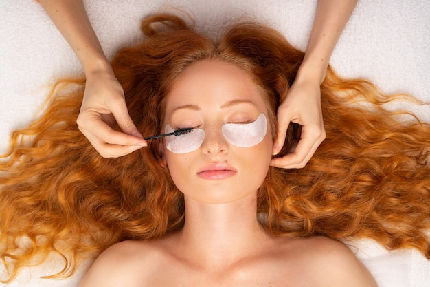 Piękna rudowłosa kobieta z kręconymi włosami kosmetyczka ręce okulary z pędzelkiem do rzęs