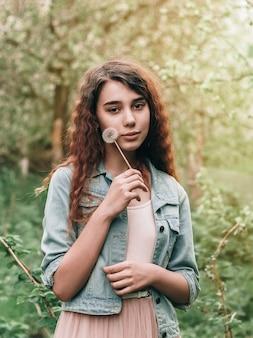 Piękna rudowłosa kręcona dziewczyna dmuchająca mniszek lekarski w wiosennym ogrodzie