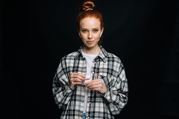 Piękna rudowłosa młoda kobieta w bezprzewodowych słuchawkach patrząca na kamerę na na białym tle
