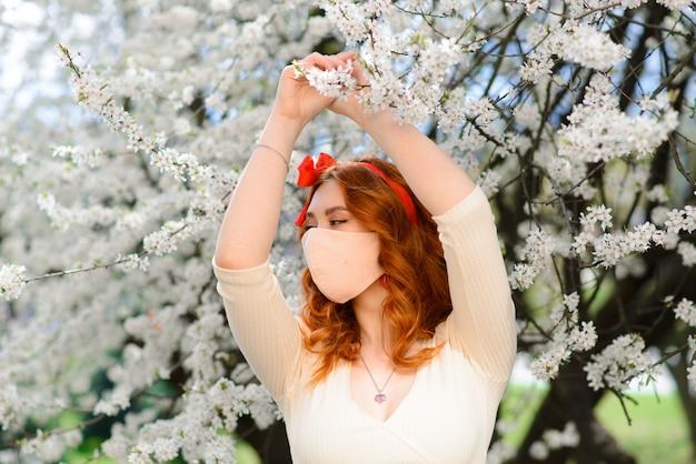 Piękna rudowłosa młoda kobieta w ochronnej masce stoi w pobliżu kwitnącej wiśni podczas kwarantanny z powodu pandemii koronawirusa