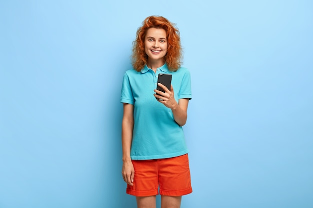 Piękna rudowłosa nastolatka używa smartfona, instaluje nową aplikację