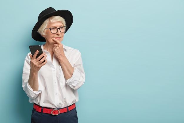 Piękna rudowłosa pomarszczona kobieta trzyma podbródek, rozgląda się w zamyśleniu, trzyma nowoczesny telefon komórkowy, rozważa treść wiadomości, ubrana w modne dla emerytów ciuchy. puste miejsce