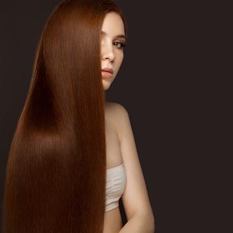 Piękna rudowłosa z idealnie gładkimi włosami i klasycznym makijażem. piękna twarz.