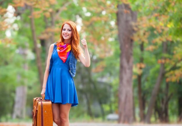 Piękna rudzielec dziewczyna z walizką w parku.