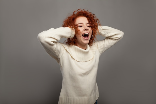 Piękna rudzielec kędzierzawa kobieta krzyczy w szoku