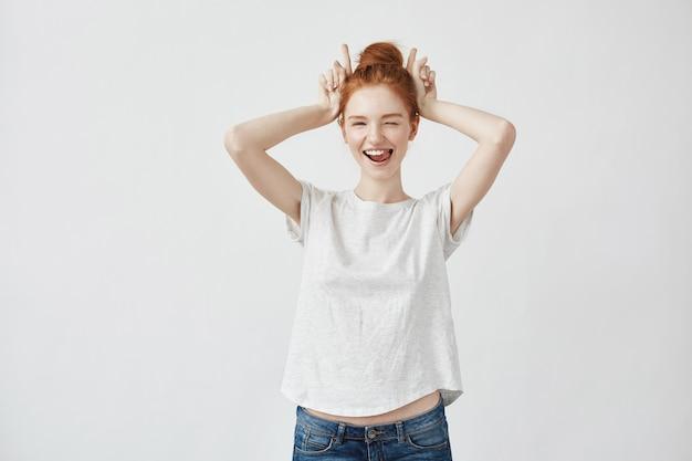 Piękna rudzielec kobieta mruga uśmiecha się pokazywać zając ręki.