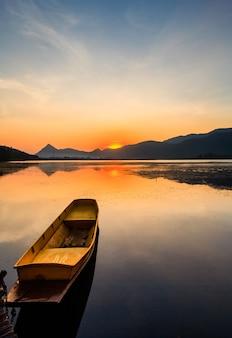 Piękna rybak łódź w jeziora i wschodu słońca nieba tle