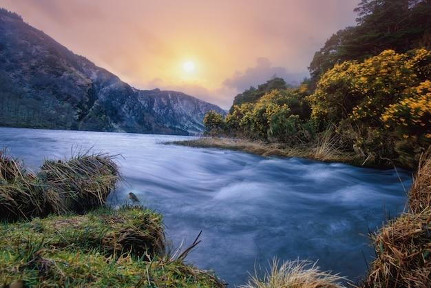 Piękna rzeka otoczona roślinnością i kwiatami przez góry pod kolorowym niebem