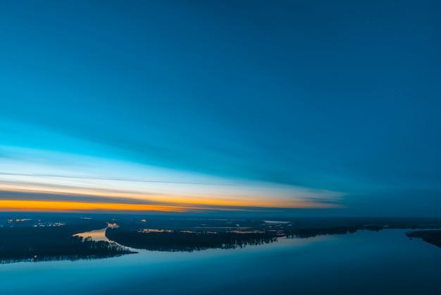 Piękna rzeka z dużą wyspą z drzewami pod predawn niebem. jasny pomarańczowy pasek w malowniczym pochmurnym niebie. wczesne błękitne niebo odbite w wodzie. kolorowy poranek atmosferyczny obraz majestatycznej przyrody.