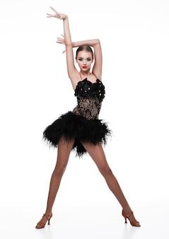 Piękna sala balowa tancerza dziewczyna w eleganckiej pozy czerni sukni na bielu