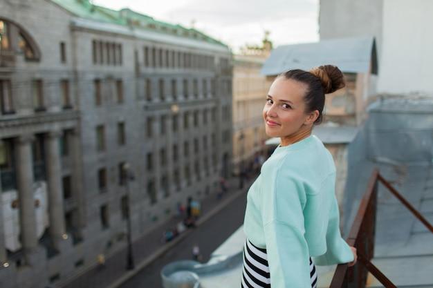 Piękna samotna dziewczyna stoi na dachu.