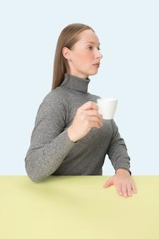 Piękna samotna kobieta siedzi i wygląda smutno, trzymając w ręku filiżankę kawy. zbliżenie stonowanych portret w stylu minimalizmu