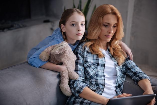 Piękna samotna zdenerwowana dziewczyna czeka na uwagę matki w domu i przytula rodzica, podczas gdy matka surfuje po internecie i korzysta z tabletu