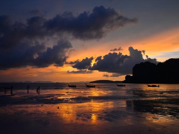 Piękna scena zachód słońca z dramatycznym niebem nad morzem plaży z tradycyjnymi łodziami longtail w tajlandii