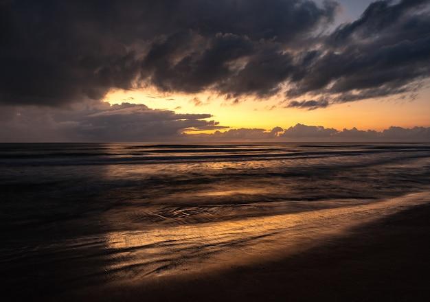 Piękna sceneria falującego morza pod zachmurzonym niebem o wschodzie słońca
