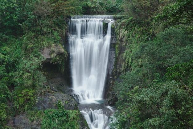 Piękna sceneria głębokiego wodospadu w pobliżu formacji skalnych w lesie na tajwanie