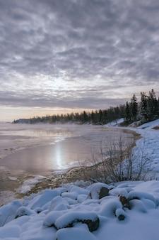 Piękna sceneria jeziora otoczonego wysokimi skalistymi górami pokrytymi śniegiem w promieniach słońca