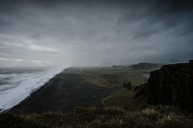 Piękna sceneria morza otoczona formacjami skalnymi spowitymi mgłą na islandii