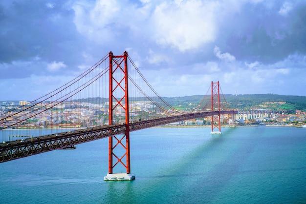 Piękna sceneria mostu 25 de abril w portugalii pod zapierającymi dech w piersiach formacjami chmur