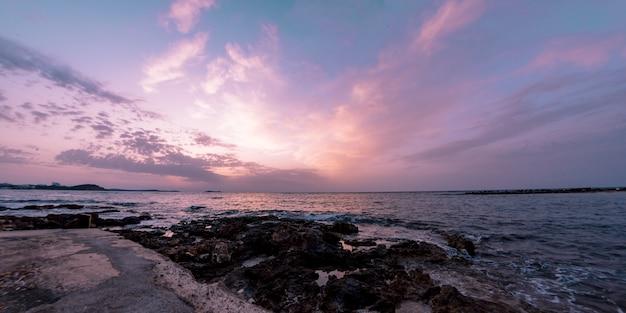 Piękna sceneria skalistego wybrzeża i morza podczas zachodu słońca