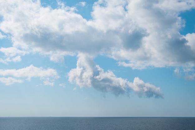 Piękna sceneria spokojnego morza pod zapierającymi dech w piersiach białymi chmurami