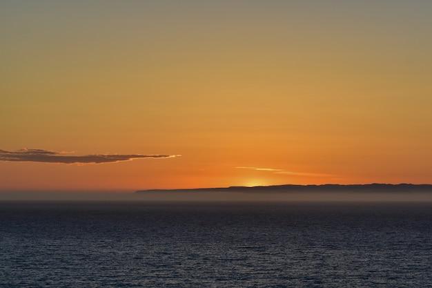 Piękna sceneria spokojnego morza z zapierającym dech w piersiach zachodem słońca w tle