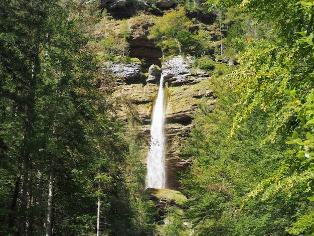 Piękna sceneria wodospadu, który przechodzi przez porośnięte mchem skały w lesie