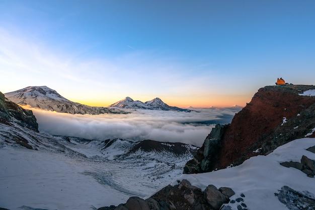 Piękna sceneria wysokich skalistych gór pokrytych śniegiem pod zapierającym dech w piersiach niebem