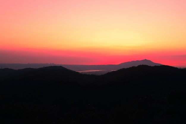 Piękna sceneria wysokich trawiastych wzgórz pod zapierającym dech w piersiach zachodem słońca
