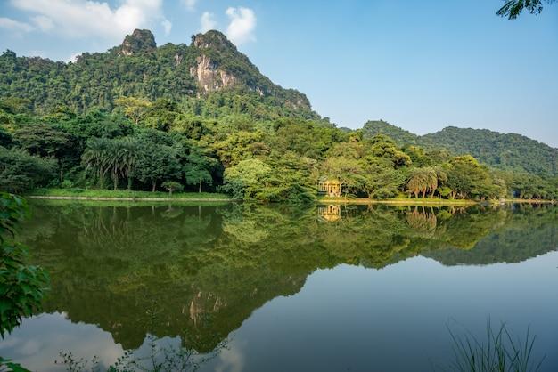 Piękna sceneria zielonych drzew i wysokich gór odbija się w jeziorze