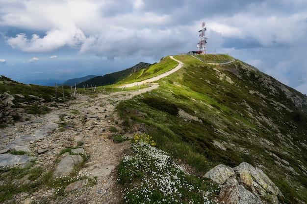 Piękna ścieżka otoczona naturą i pod ciężkimi chmurami w kierunku stacji pogodowej na górze turó de l'home w hiszpanii