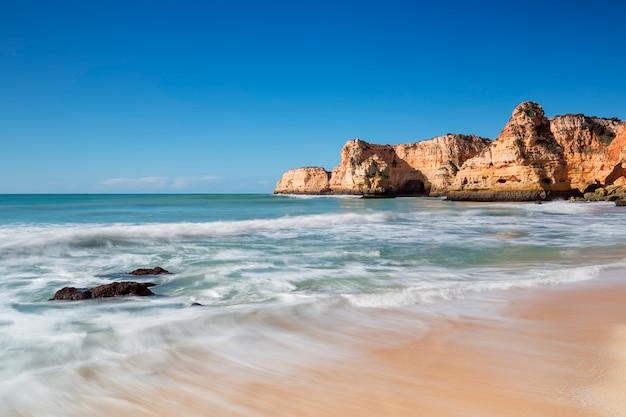 Piękna seascape plaża w albufeira. niewyraźne fale.