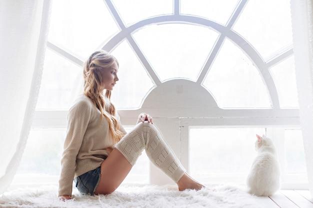 Piękna seksowna blondynka siedzi w oknie wraz z kotem