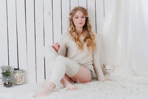 Piękna seksowna blondynka siedzi z kotem