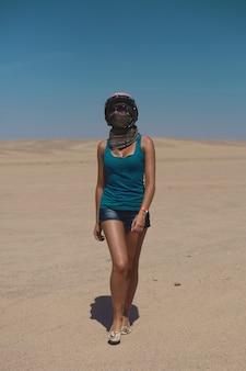 Piękna seksowna blondynka w kasku i okularach przeciwsłonecznych, ubrana w szorty i koszulkę, chodzenie po pustyni.