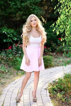 Piękna seksowna blondynki kobieta ubierająca w drelichowych błękitnych skrótach.