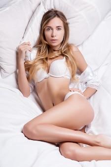 Piękna seksowna blondynki kobieta w białej bieliźnie kłama na łóżku