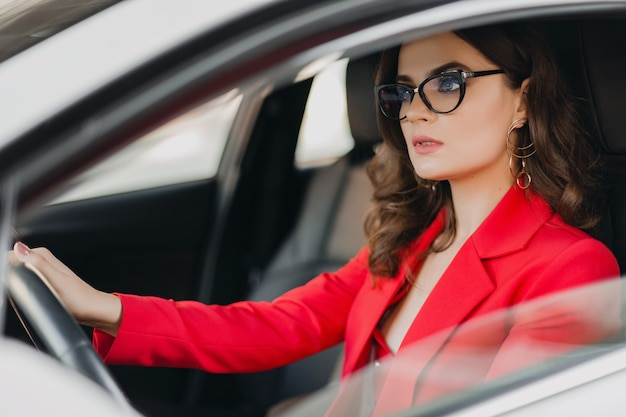 Piękna seksowna bogata biznesowa kobieta w czerwonym garniturze, jazda białym samochodem, w okularach, biznes dama styl