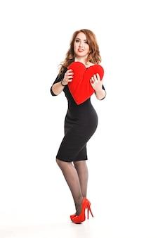 Piękna seksowna brunetka kobieta obecny czerwone serce, walentynki. elegancki model dziewczyny z długimi falowanymi włosami, makijaż. pani w luksusowej sukience na białym tle.