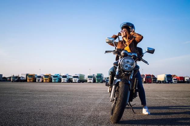 Piękna seksowna brunetka kobieta w skórzanej kurtce siedzi na motocyklu w stylu retro przygotowuje się do jazdy