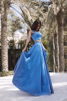 Piękna seksowna brunetka stoi przy basenie w długiej niebieskiej sukience rozdzielonej, kobieta z długimi włosami, idealnym ciałem i ładną buzią, makijaż, pod palmami