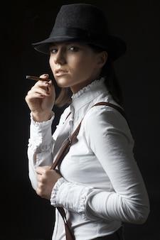 Piękna seksowna brunetki kobieta w kapeluszowym dymienie papierosie