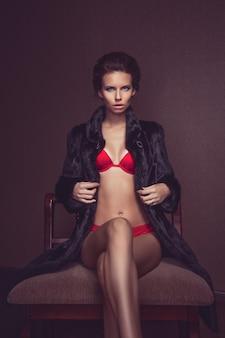 Piękna seksowna długowłosa brunetka kobieta w czerwonej bieliźnie i futro pozowanie